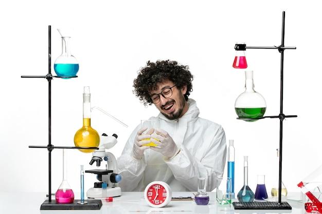 Vue de face jeune homme scientifique en costume spécial assis avec des solutions sur un mur blanc clair