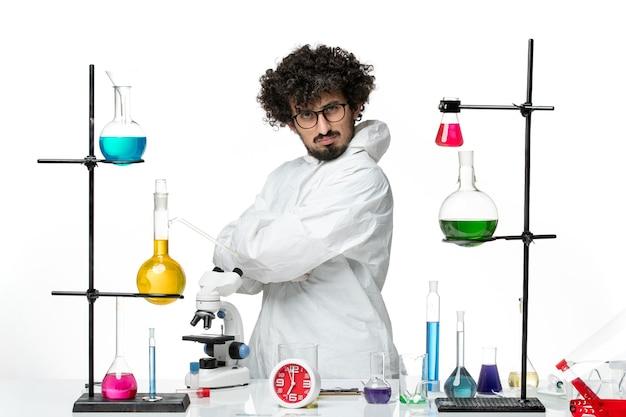 Vue de face jeune homme scientifique en costume spécial blanc debout autour de la table avec des solutions