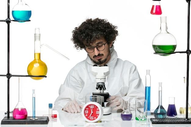 Vue de face jeune homme scientifique en costume spécial blanc essayant d'utiliser un microscope