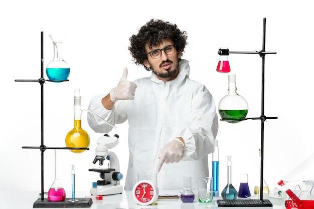 Vue de face jeune homme scientifique en costume spécial blanc posant sur blanc bureau laboratoire science covid- chimie pandémique