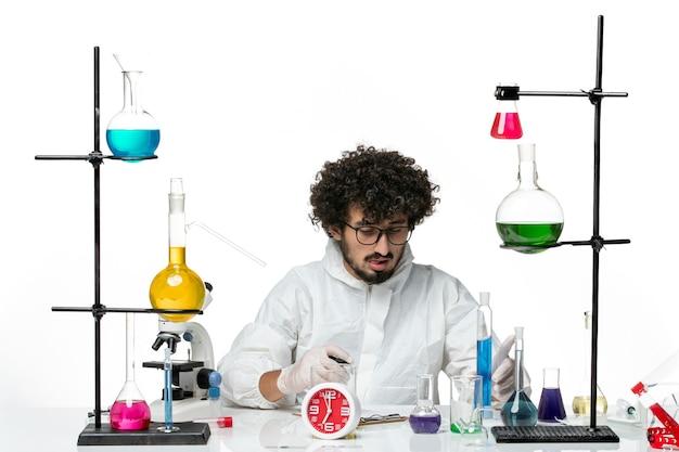 Vue de face jeune homme scientifique en costume spécial blanc tenant une solution bleue et écrire des notes sur un mur blanc