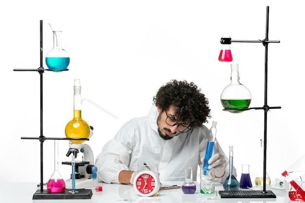Vue de face jeune homme scientifique en costume spécial blanc tenant une solution bleue