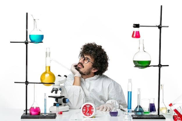 Vue de face jeune homme scientifique en costume spécial blanc travaillant avec des solutions et de la réflexion