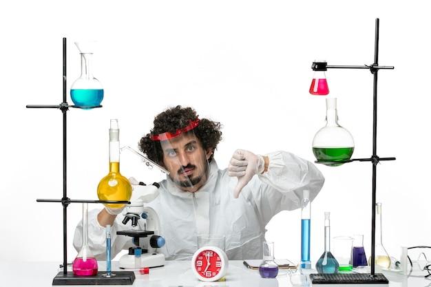 Vue de face jeune homme scientifique en costume spécial avec un casque de protection à l'aide d'un microscope sur blanc bureau science laboratoire covid chimie male