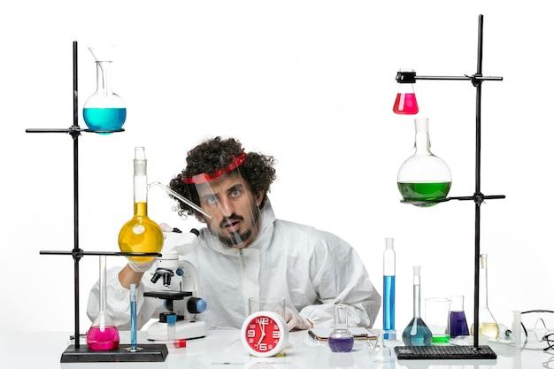 Vue de face jeune homme scientifique en costume spécial avec un casque de protection à l'aide d'un microscope sur mur blanc science laboratoire covid chimie male