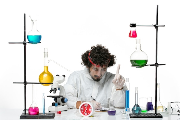 Vue de face jeune homme scientifique en costume spécial avec casque de protection écrit des notes sur blanc bureau science laboratoire covid chimie mâle