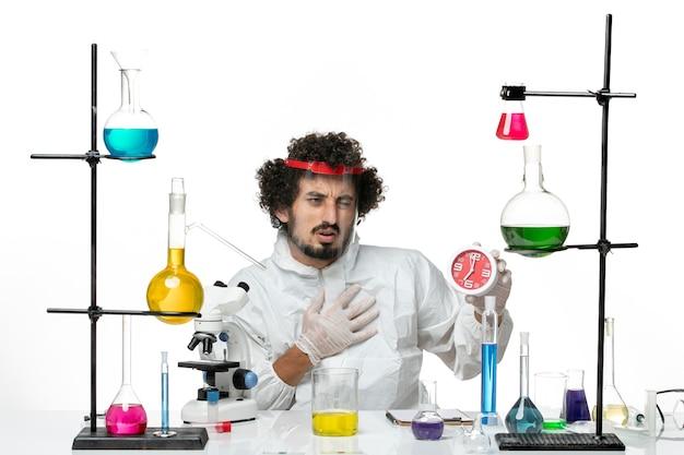 Vue de face jeune homme scientifique en costume spécial avec casque de protection tenant une horloge sur un mur blanc clair