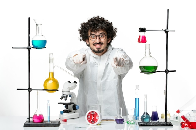 Vue de face jeune homme scientifique en costume spécial debout autour de la table avec des solutions sur un bureau blanc