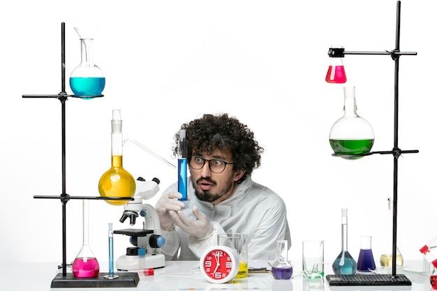 Vue de face jeune homme scientifique en costume spécial holding flask avec solution sur mur blanc