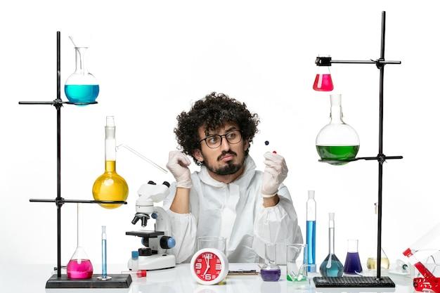 Vue de face jeune homme scientifique en costume spécial tenant des échantillons sur un mur blanc