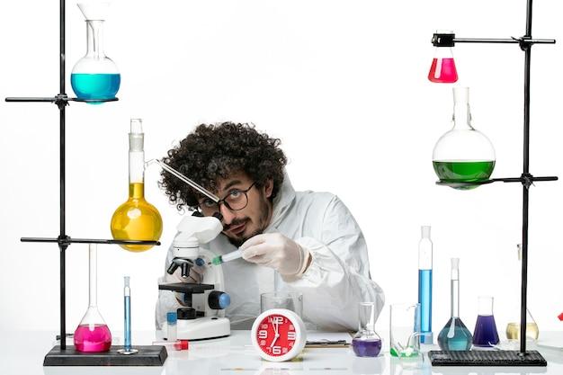 Vue de face jeune homme scientifique en costume spécial travaillant avec injection sur mur blanc