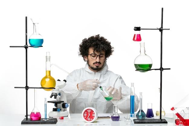 Vue de face jeune homme scientifique en costume spécial travaillant avec injection et solution sur fond blanc