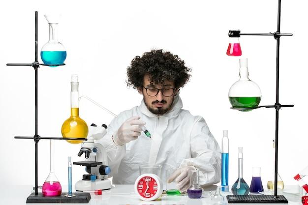 Vue de face jeune homme scientifique en costume spécial travaillant avec injection et solution sur white desk virus covid- laboratoire chimie science