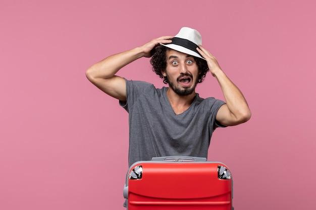 Vue de face jeune homme se préparant pour des vacances en chapeau sur l'espace rose