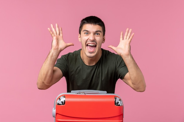 Vue de face jeune homme se préparant pour des vacances criant sur un espace rose