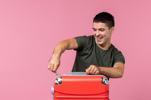 Vue de face jeune homme se préparant pour les vacances et fermant son sac sur un espace rose