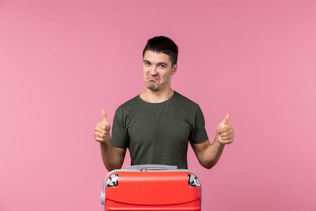 Vue de face jeune homme se préparant pour des vacances avec un grand sac sur l'espace rose