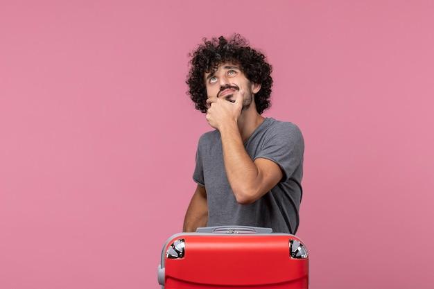 Vue de face jeune homme se préparant pour les vacances et réfléchissant à l'espace rose
