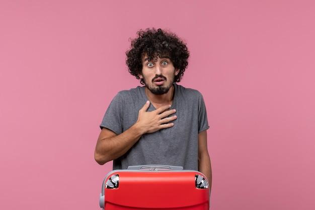 Vue de face jeune homme se préparant pour des vacances avec un sac sur un bureau rose