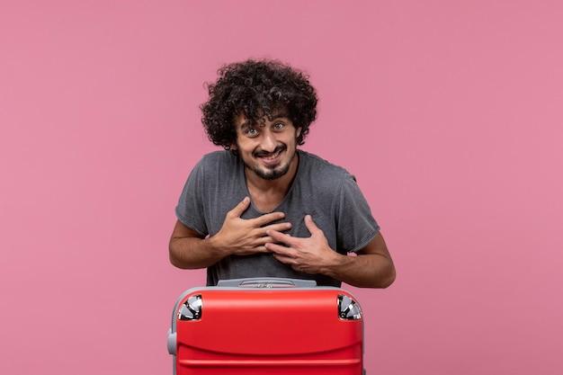 Vue de face jeune homme se préparant pour les vacances avec un sac sur un espace rose clair