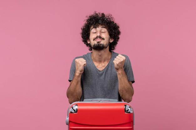 Vue de face jeune homme se préparant pour les vacances se réjouissant de l'espace rose