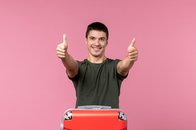 Vue de face jeune homme se préparant pour des vacances souriant sur un espace rose