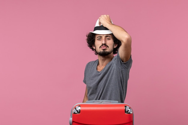 Vue de face jeune homme se préparant pour des vacances tenant un chapeau sur l'espace rose