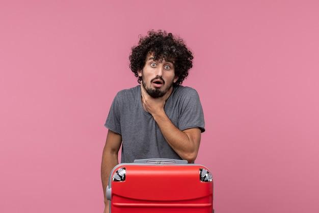 Vue de face jeune homme se préparant pour les vacances tenant sa gorge sur un espace rose