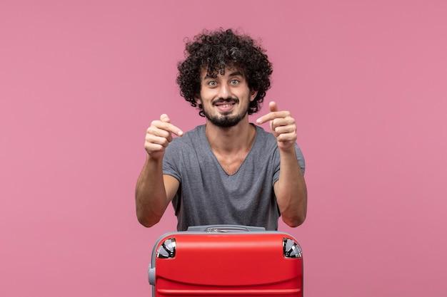 Vue de face jeune homme se préparant pour un voyage sur un espace rose clair