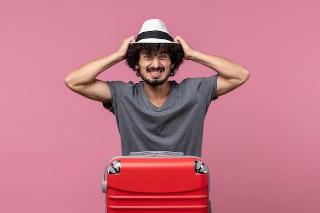 Vue de face jeune homme se préparant pour le voyage et portant un chapeau sur l'espace rose