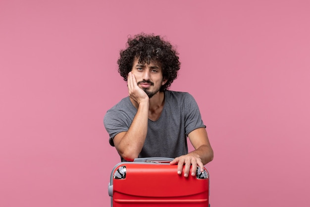 Vue de face jeune homme se préparant pour un voyage avec un sac sur un espace rose clair