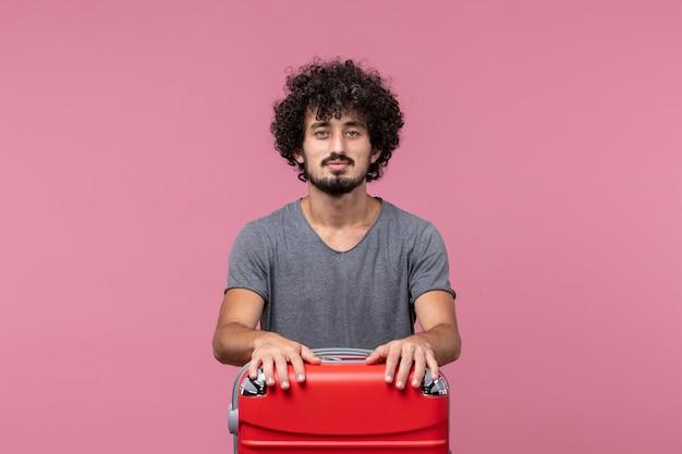 Vue de face jeune homme se préparant pour un voyage avec un sac sur l'espace rose