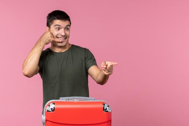 Vue de face jeune homme se préparant pour un voyage avec un sac rouge sur un espace rose clair