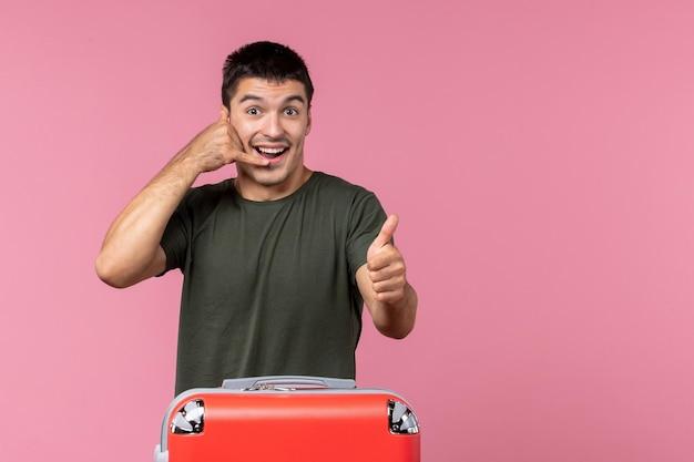 Vue de face jeune homme se préparant pour un voyage avec un sac rouge sur un espace rose