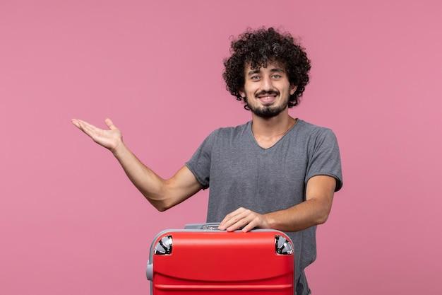 Vue de face jeune homme se préparant pour un voyage souriant sur un espace rose
