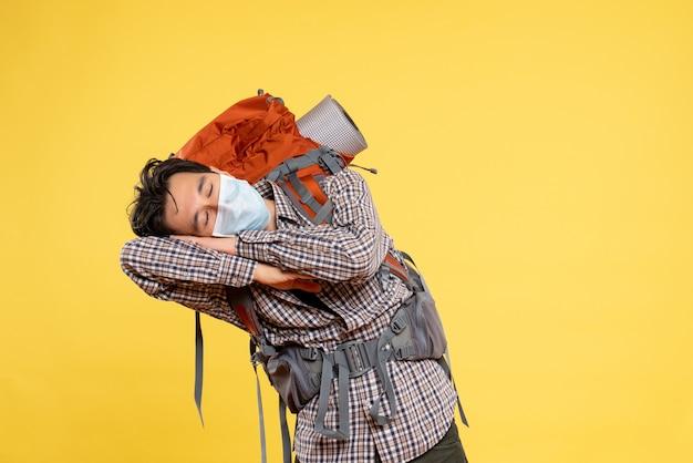 Vue de face jeune homme se préparant à la randonnée en masque dormir sur jaune