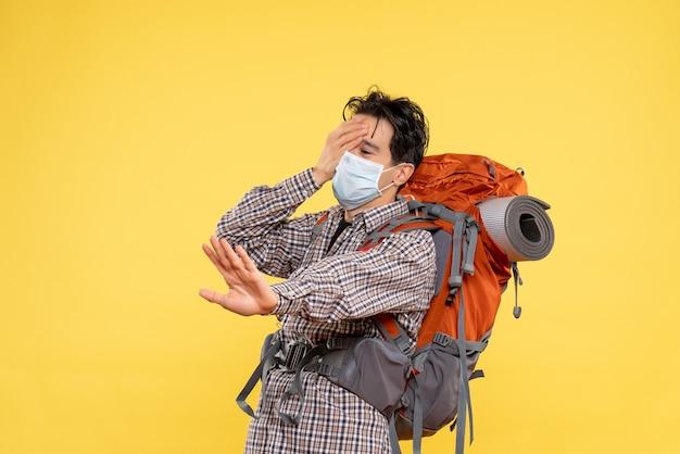 Vue de face jeune homme se préparant à la randonnée en masque sur jaune