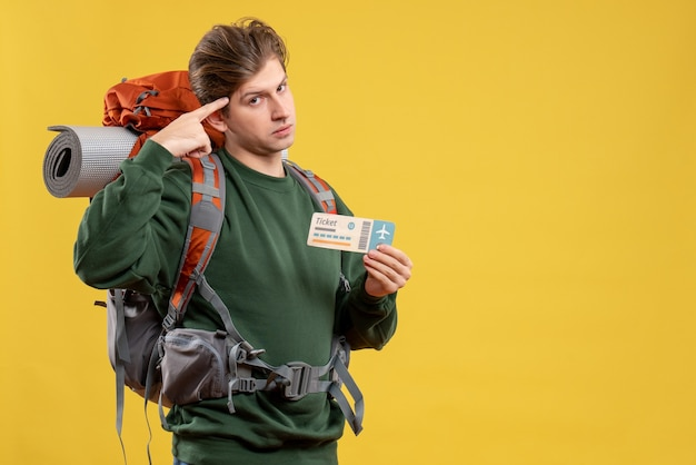 Vue de face jeune homme se préparant à la randonnée tenant un billet