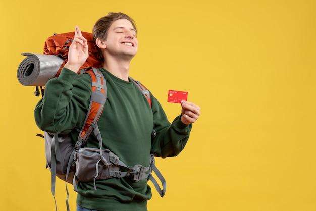 Vue de face jeune homme se préparant à la randonnée tenant une carte bancaire rouge