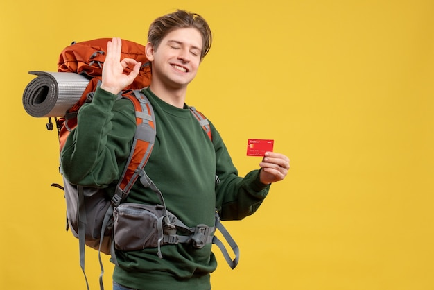 Vue de face jeune homme se préparant à la randonnée tenant une carte bancaire