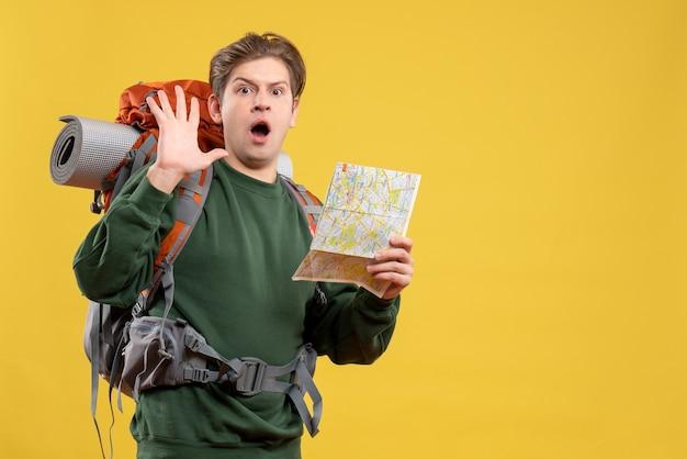 Vue de face jeune homme se préparant à la randonnée tenant la carte