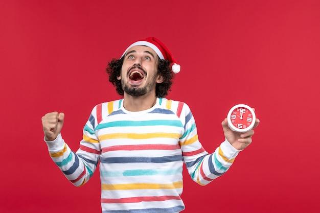 Vue de face jeune homme se réjouissant pour les nouvelles années à venir sur le mur rouge temps rouge vacances du nouvel an