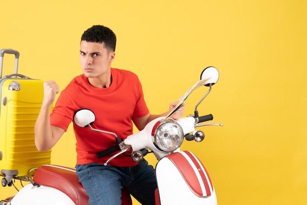 Vue de face jeune homme sérieux sur cyclomoteur montrant punch