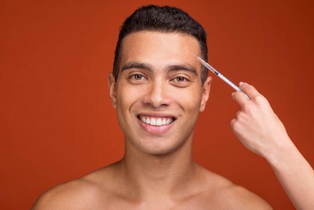 Vue de face jeune homme et seringue remplie de botox