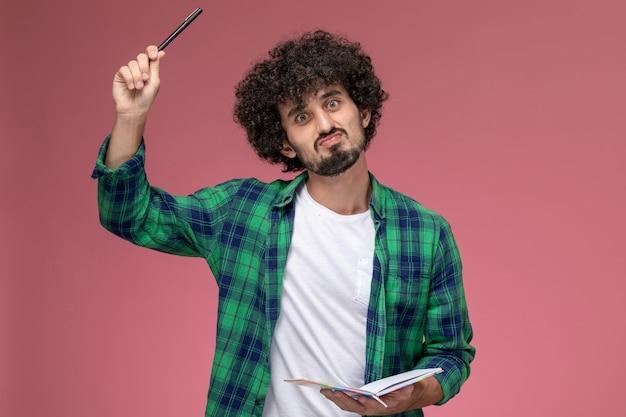 Vue de face jeune homme soulevant son stylo