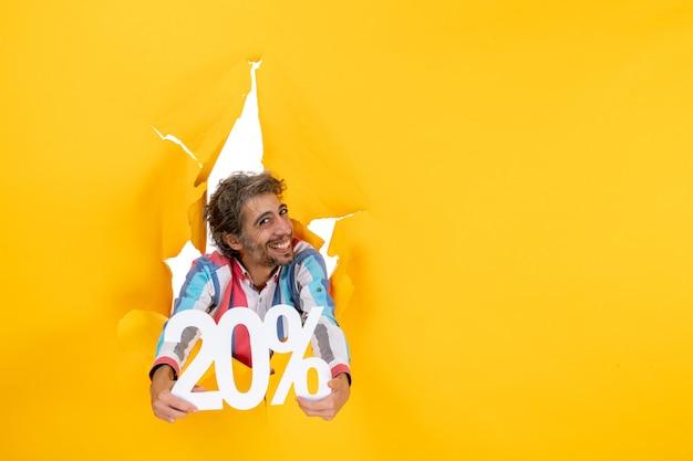 Vue de face d'un jeune homme souriant montrant vingt pour cent dans un trou déchiré dans du papier jaune