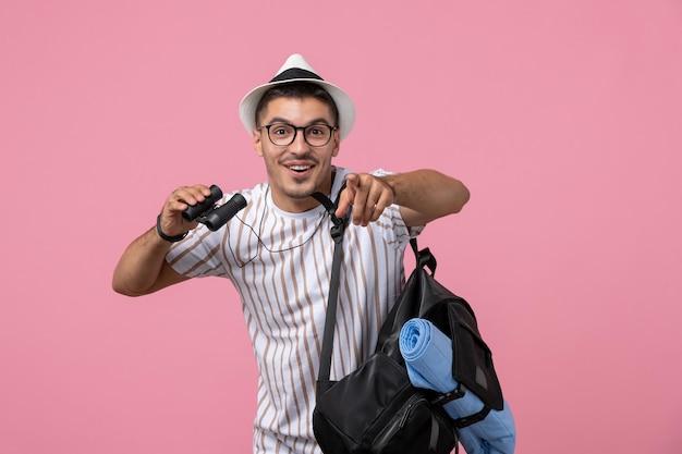 Vue de face jeune homme en t-shirt blanc à l'aide de jumelles sur fond rose