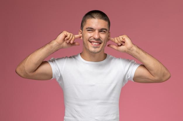 Vue de face jeune homme en t-shirt blanc collant ses oreilles avec sourire sur fond rose