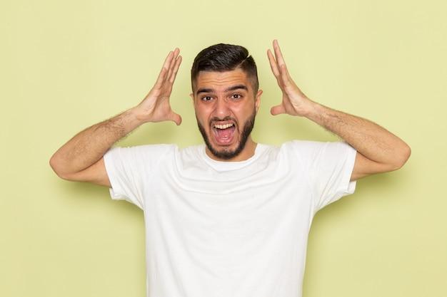 Une vue de face jeune homme en t-shirt blanc hurlant