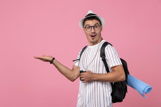 Vue de face jeune homme en t-shirt blanc avec des jumelles sur fond rose clair